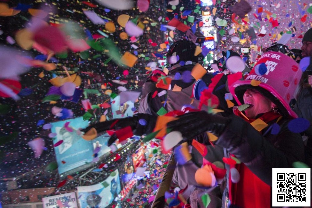 Revellers toss confetti over Times Square from a hotel balcony as the clock strikes midnight during New Year's Eve celebrations in New York